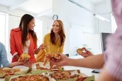 吃薄饼的愉快的企业队在办公室 库存照片