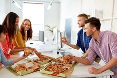 吃薄饼的愉快的企业队在办公室 免版税图库摄影