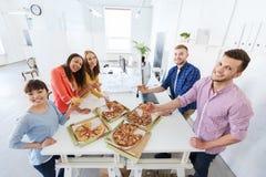 吃薄饼的愉快的企业队在办公室 库存图片