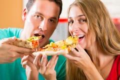 吃薄饼的男人和妇女 免版税库存图片