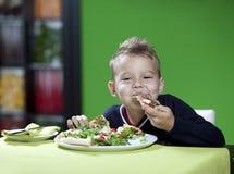 吃薄饼的男孩 免版税图库摄影