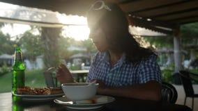 吃薄饼的行家女孩在一室外在与透镜火光的日落期间影响的餐馆 3840x2160 影视素材