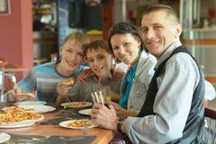 吃薄饼的逗人喜爱的家庭 免版税库存照片