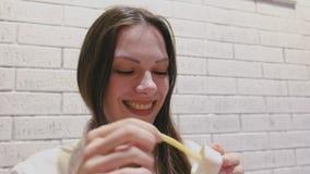 吃薯条用在咖啡馆的乳酪调味料的妇女 股票录像
