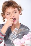 吃蛋白软糖的小女孩 免版税库存照片