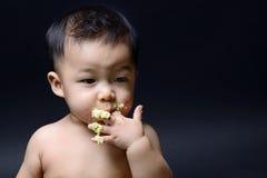 吃蛋糕用他的手的逗人喜爱的亚裔婴孩 免版税库存图片