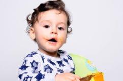 吃蛋糕的一个逗人喜爱的婴孩的画象做混乱 免版税图库摄影