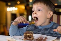 吃蛋糕的大满嘴小男孩 免版税库存图片