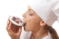 吃蛋糕的妇女厨师 免版税库存图片