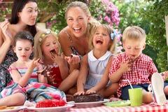 吃蛋糕的子项和母亲在Outd 免版税库存图片