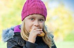 吃蛋糕的小美丽的白肤金发的女孩在公园 免版税库存图片