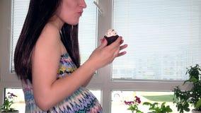 吃蛋糕的微笑的孕妇 股票录像