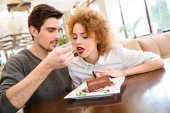 吃蛋糕的愉快的夫妇在餐馆 图库摄影