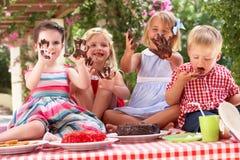 吃蛋糕的组子项在室外茶会 免版税库存图片