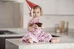 吃蛋糕的逗人喜爱的女婴 免版税库存照片