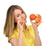 吃蜜桔普通话果子的妇女 库存图片