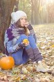 吃蜜桔的女孩在公园 免版税库存照片