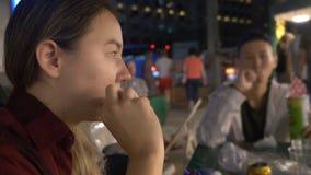 吃街道食物的年轻亚裔女孩在晚上户外 股票视频
