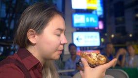 吃街道食物的年轻亚裔女孩在晚上户外 股票录像
