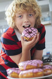 吃被冰的多福饼的男孩在厨房里 免版税图库摄影