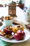 吃被烘烤的苹果用核桃、蜂蜜和桂香,圣诞节 免版税图库摄影