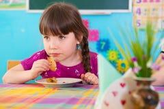 吃被烘烤的苹果的逗人喜爱的女孩在幼儿园 免版税库存照片
