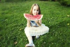 吃西瓜的女孩在庭院里 库存照片