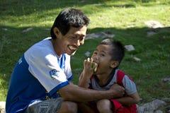 吃西瓜和他的爸爸的年轻印度尼西亚男孩 免版税库存图片