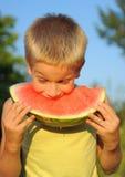 吃西瓜年轻人的男孩 免版税库存图片