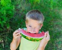 吃西瓜年轻人的男孩 库存照片