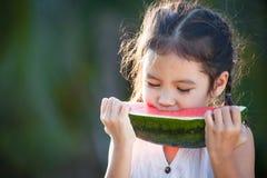 吃西瓜新鲜水果的逗人喜爱的亚裔小孩女孩 免版税图库摄影