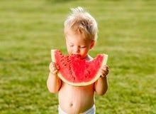 吃西瓜的一个岁男婴在庭院里 免版税库存照片