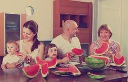 吃西瓜的三世代家庭 库存图片