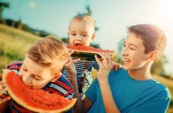 吃西瓜的三个愉快的微笑的男孩在公园 免版税库存图片