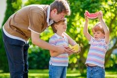 吃西瓜的两个小学龄前孩子男孩和父亲 库存照片
