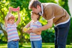 吃西瓜的两个小学龄前孩子男孩和父亲 免版税库存照片