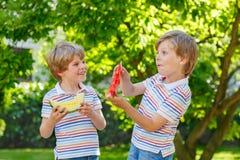 吃西瓜的两个小学龄前孩子男孩在夏天 免版税库存照片