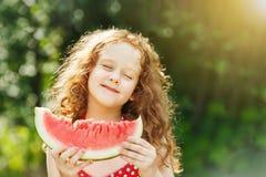 吃西瓜的女孩享用闭上她的眼睛 免版税库存照片