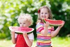 吃西瓜的孩子在庭院里 免版税图库摄影