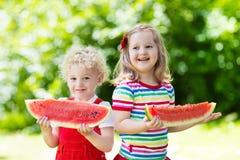 吃西瓜的孩子在庭院里 库存照片