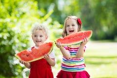 吃西瓜的孩子在庭院里 图库摄影