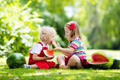 吃西瓜的孩子在庭院里 库存图片