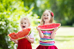 吃西瓜的孩子在庭院里 免版税库存图片