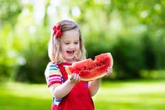 吃西瓜的小女孩在庭院里 免版税库存照片