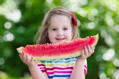 吃西瓜的小女孩在庭院里 库存图片