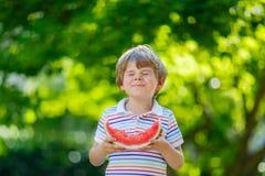 吃西瓜的小学龄前孩子男孩在夏天 图库摄影