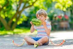 吃西瓜的小学龄前孩子男孩在夏天 库存照片