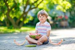 吃西瓜的小学龄前孩子男孩在夏天 免版税图库摄影