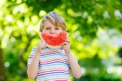 吃西瓜的小学龄前孩子男孩在夏天 免版税库存图片