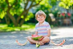 吃西瓜的小学龄前孩子男孩在夏天 库存图片